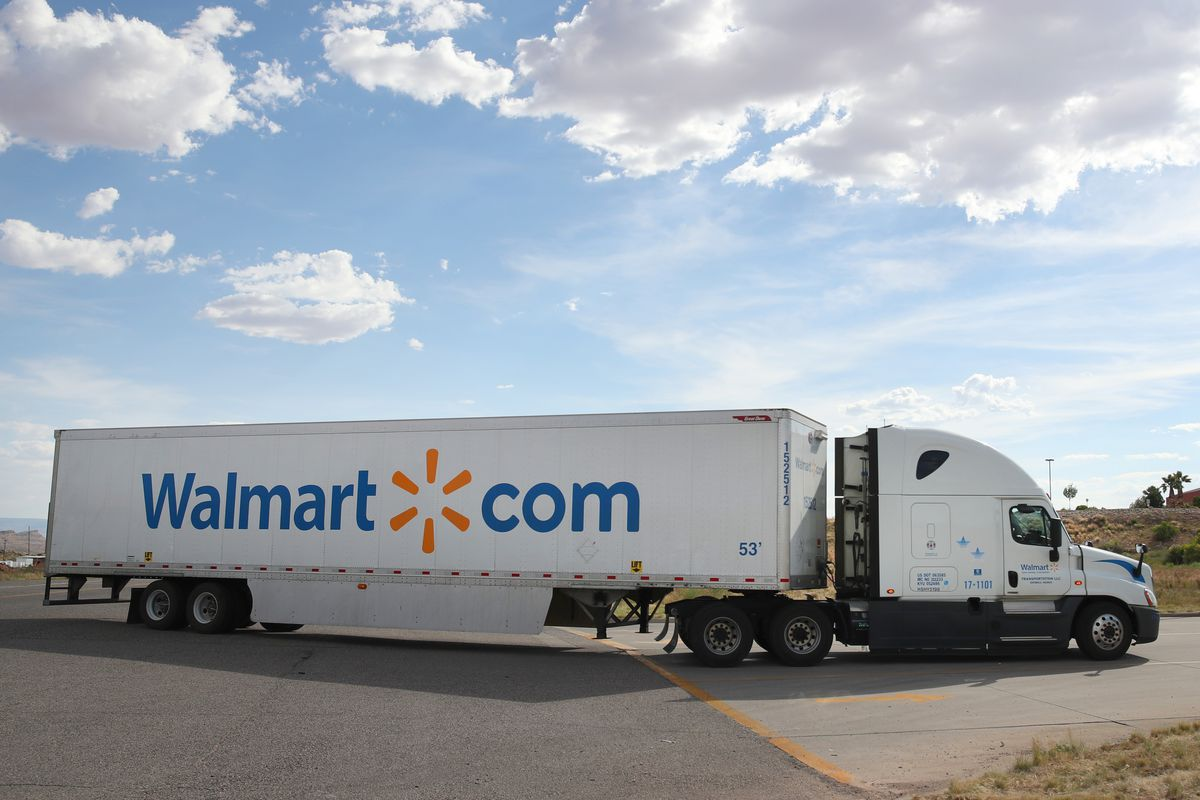 A Walmart tractor-trailer truck with walmart.com on its side leaves a parking lot.