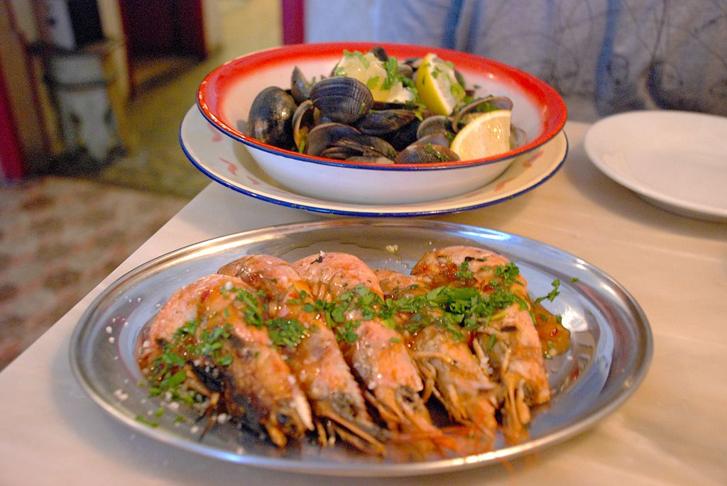 A silver dish with five head-on prawns lined up next to each other with an herbaceous sauce spread delicately over all of them. A bowl of steamed mussels sits in the background.