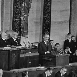 """President Lyndon B. Johnson delivers his State of the Union address to a joint session of Congress, Jan. 8, 1964. Speaking in the House of Representatives, the chief executive said on eof his aims was """"unconditional war on poverty in America."""" In background from left are: Speaker John McCormack of Massachusetts and Sen. Carl Hayden of Arizona.  (AP Photo)"""