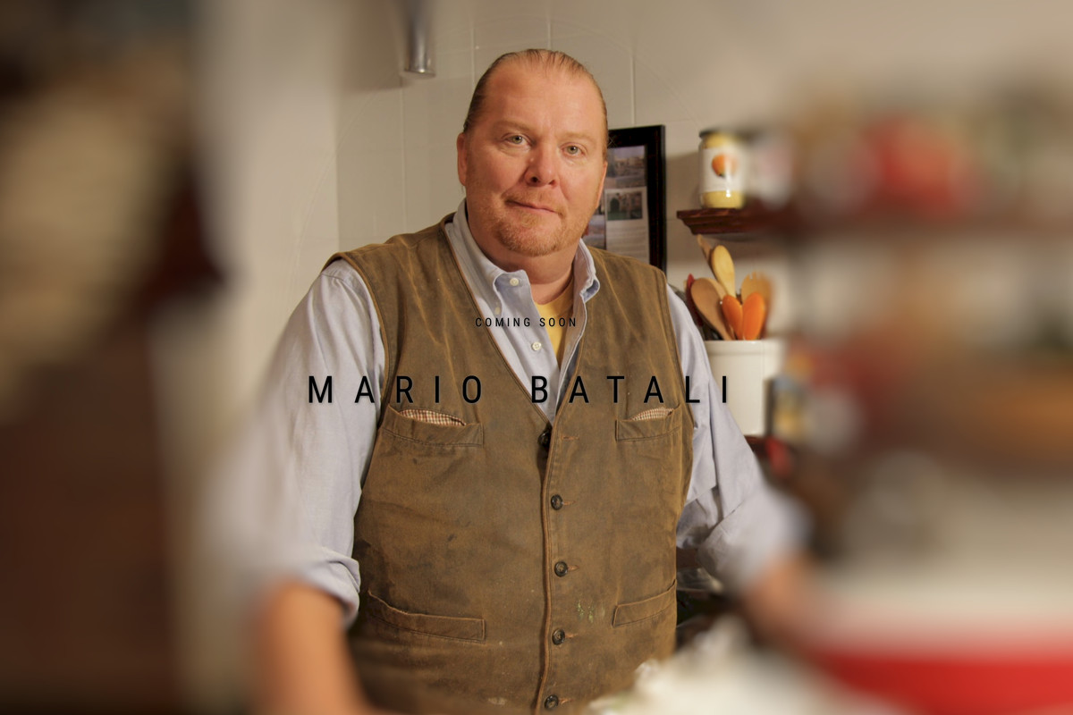 """A man, Mario Batali, stands in a kitchen. The photo is blurred on either side of the standing figure and words across the screen read """"coming soon, Mario Batali"""""""