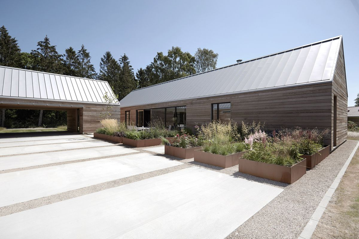 An open courtyard features a series of rectilinear planters with flowers and grass.