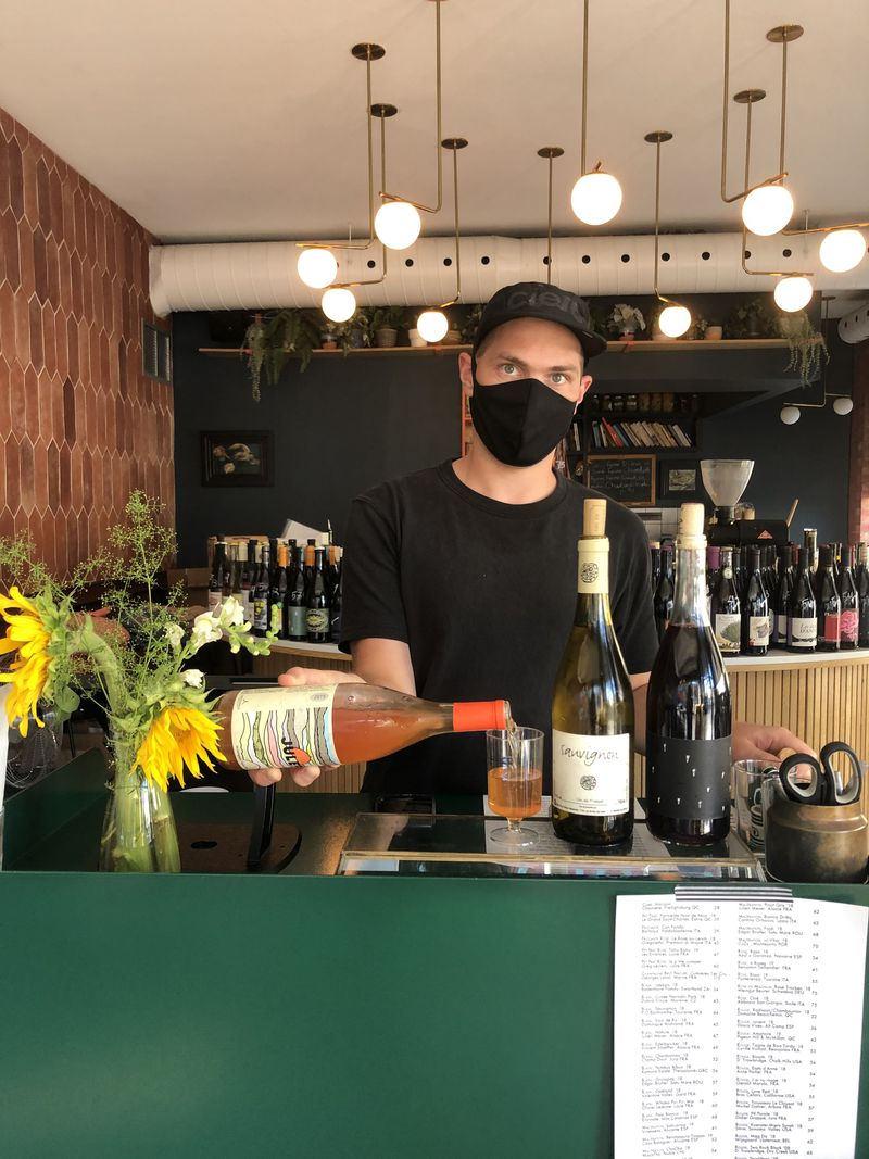 man wearing face mask pouring wine