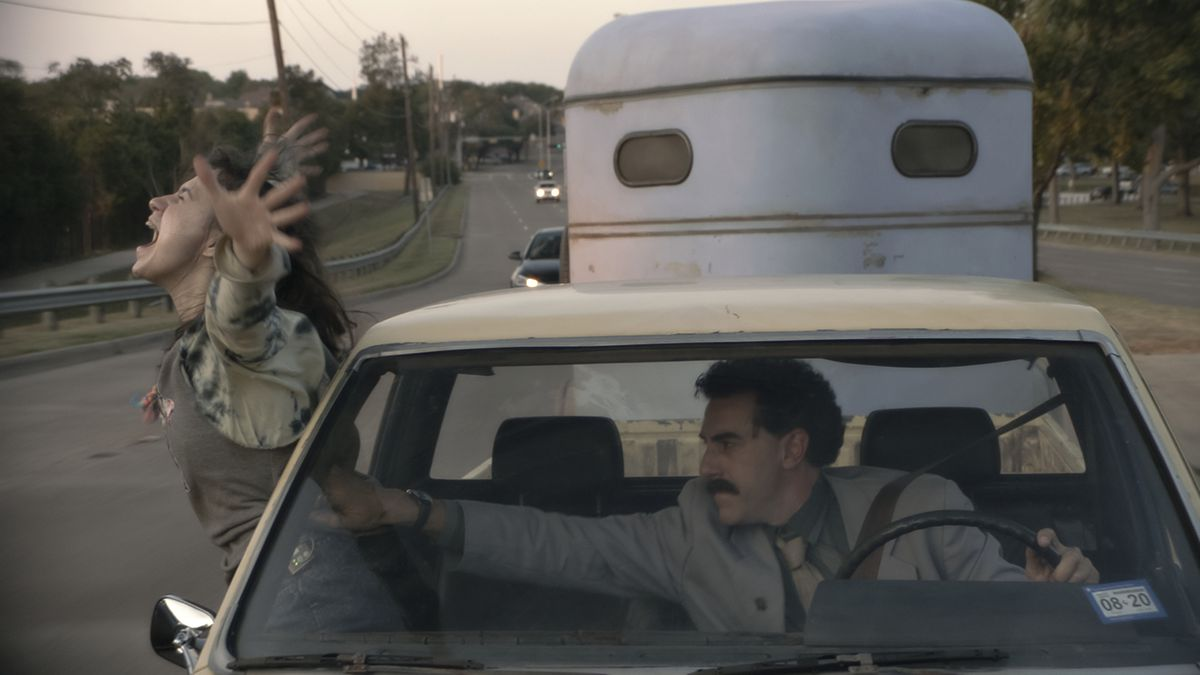 Maria Bakalova leans out of the window of a moving car as Sacha Baron Cohen tries to pull her back in in Borat Subsequent Moviefilm