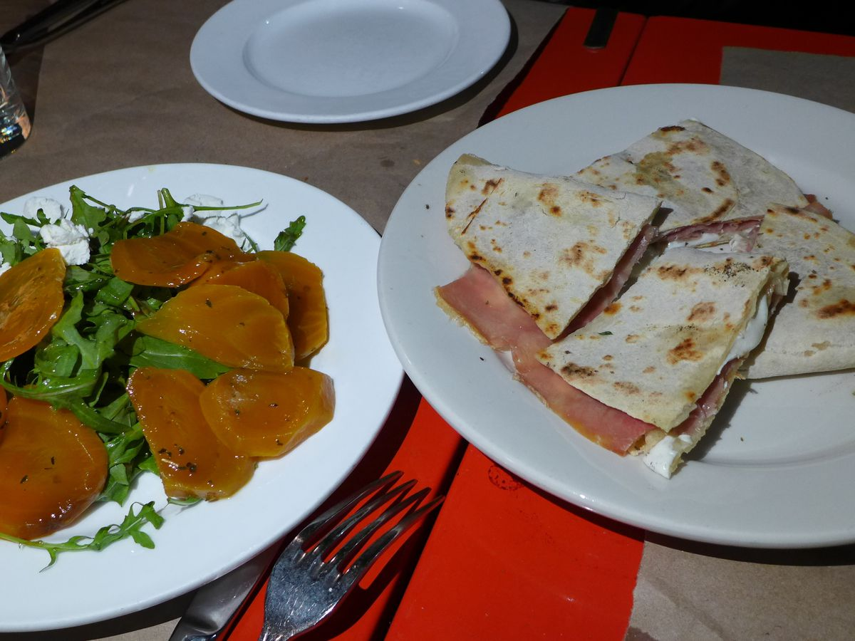 Flatbread stuffed with prosciutto and a salad of arugula and yellow tomatoes