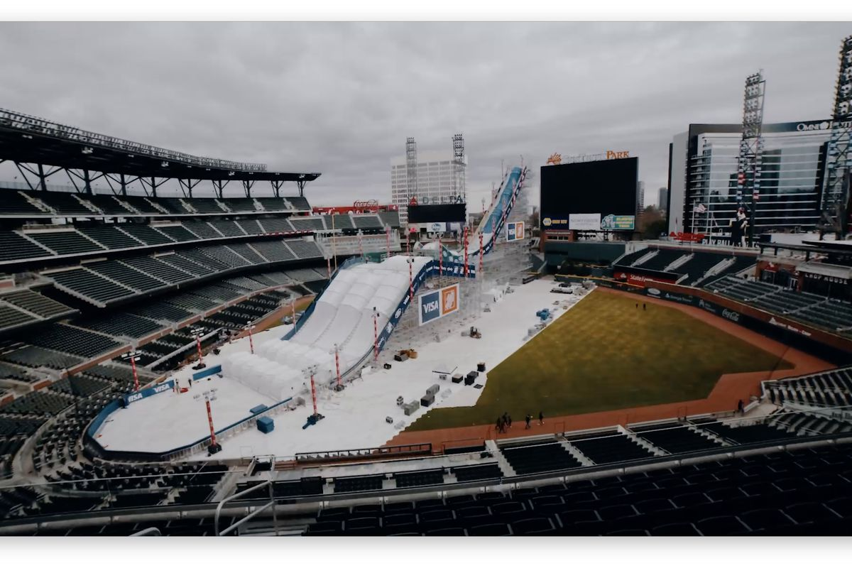 A massive white ramp being built in the middle of a baseball stadium.