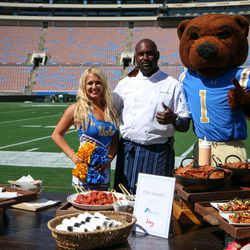 One of the chefs from Levy Restaurants poses with Joe Bruin and a member of the UCLA Spirit Squad behind the food offerings that will be available at Fish Market.