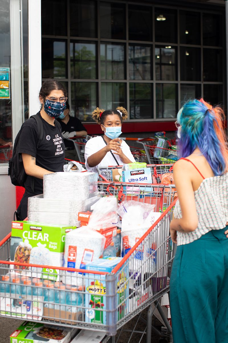 Three people stand in front of a grocery store, pushing two shopping carts filled with snacks and other supplies