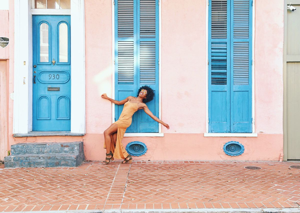A woman dancing in front of colorful doors and window shutters in the French Quarter.
