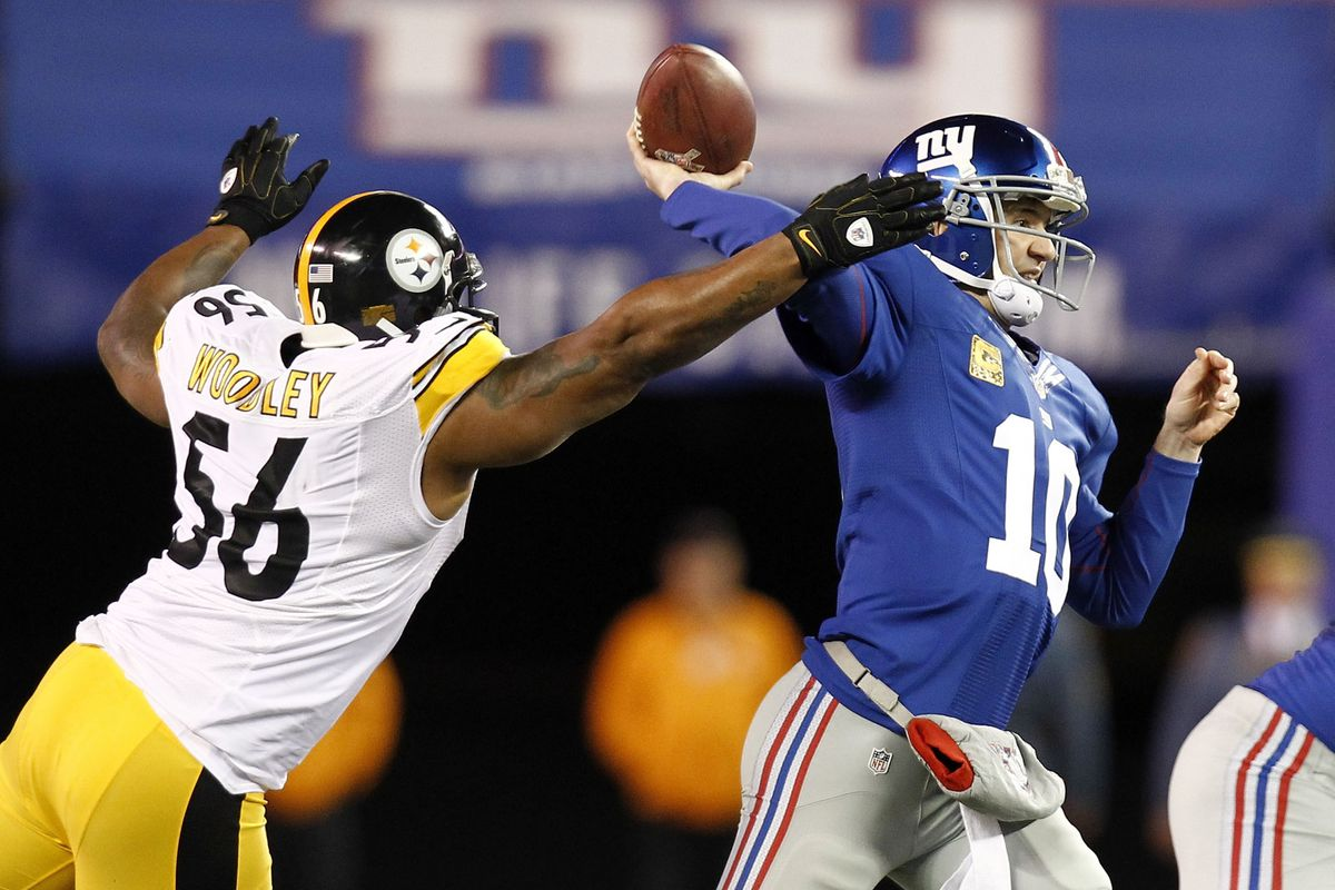 Eli Manning has his arm hit by LaMarr Woodley as he tries to pass on Sunday.
