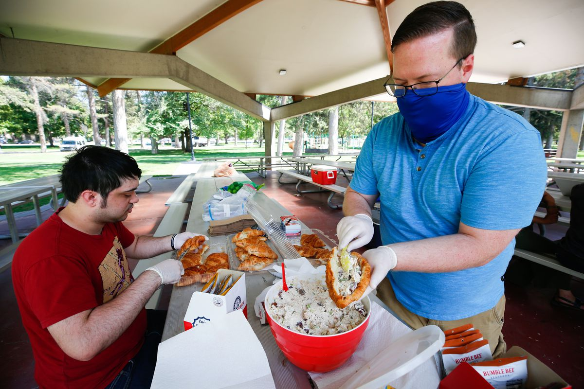 Enoch Thompson, left, cuts a croissants while Kevin McDowellfills them with chicken salad during a food donation and distribution event for Utah refugees at Liberty Park in Salt Lake City on Monday, Aug. 17, 2020 The event was organized by Walk for Peace 2020, a group of three friends who are walking from San Francisco to Washington, D.C., to promote peace and unity.
