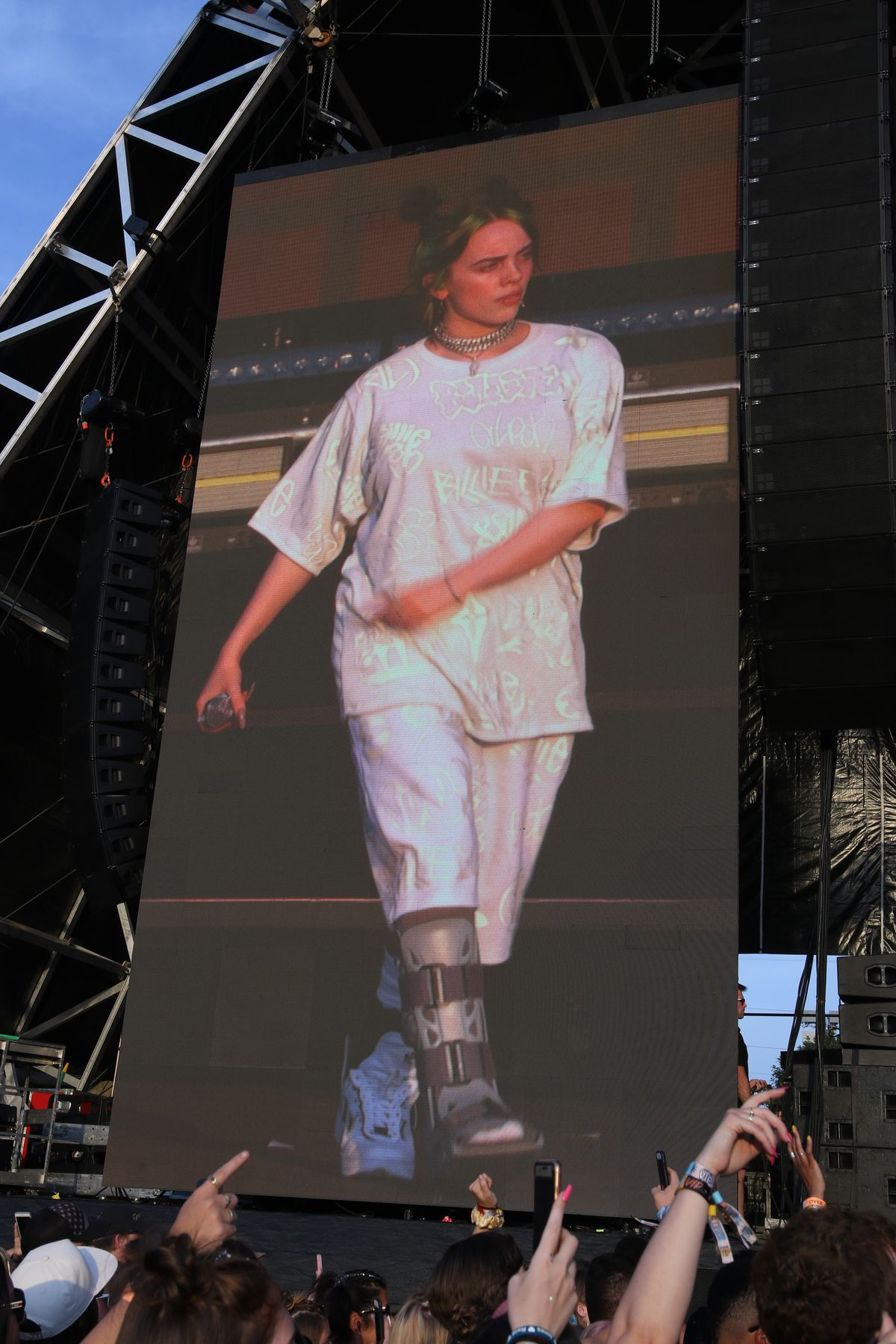 Billie Eilish, seen on one of the jumbotrons, wears a cast on her right leg.