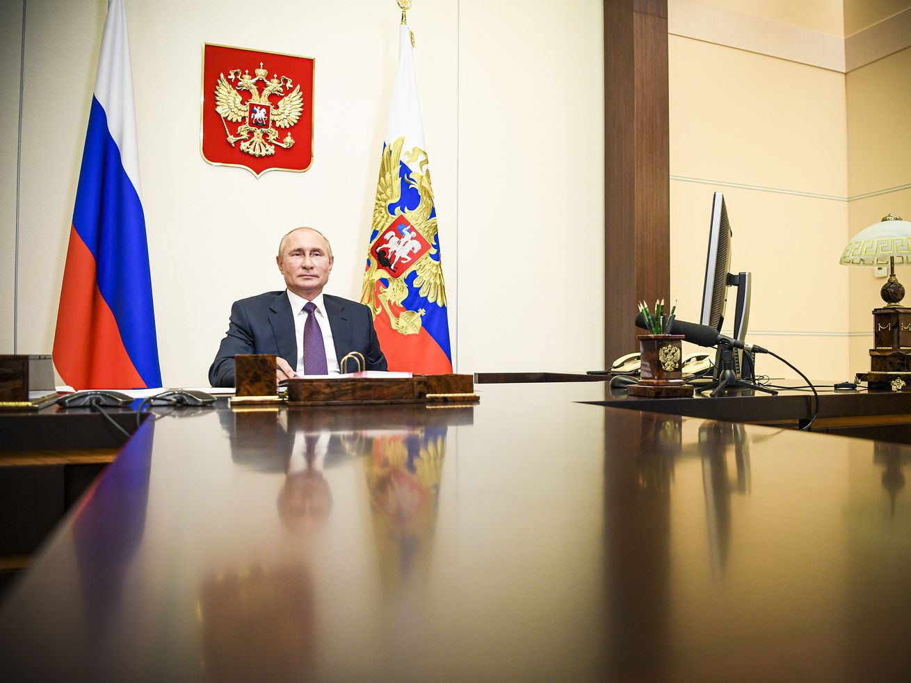 Russia's President Vladimir Putin sitting at a desk during a video conference meeting.