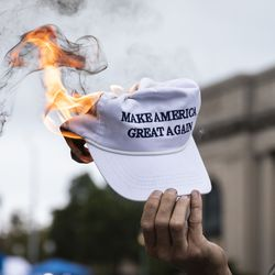 """A Black Lives Matter protester burns a """"Make America Great Again"""" hat in downtown Kenosha, Tuesday evening, Sept. 1, 2020. President Donald Trump visited Kenosha Tuesday after the police shooting of Jacob Blake led unrest in the Wisconsin city."""