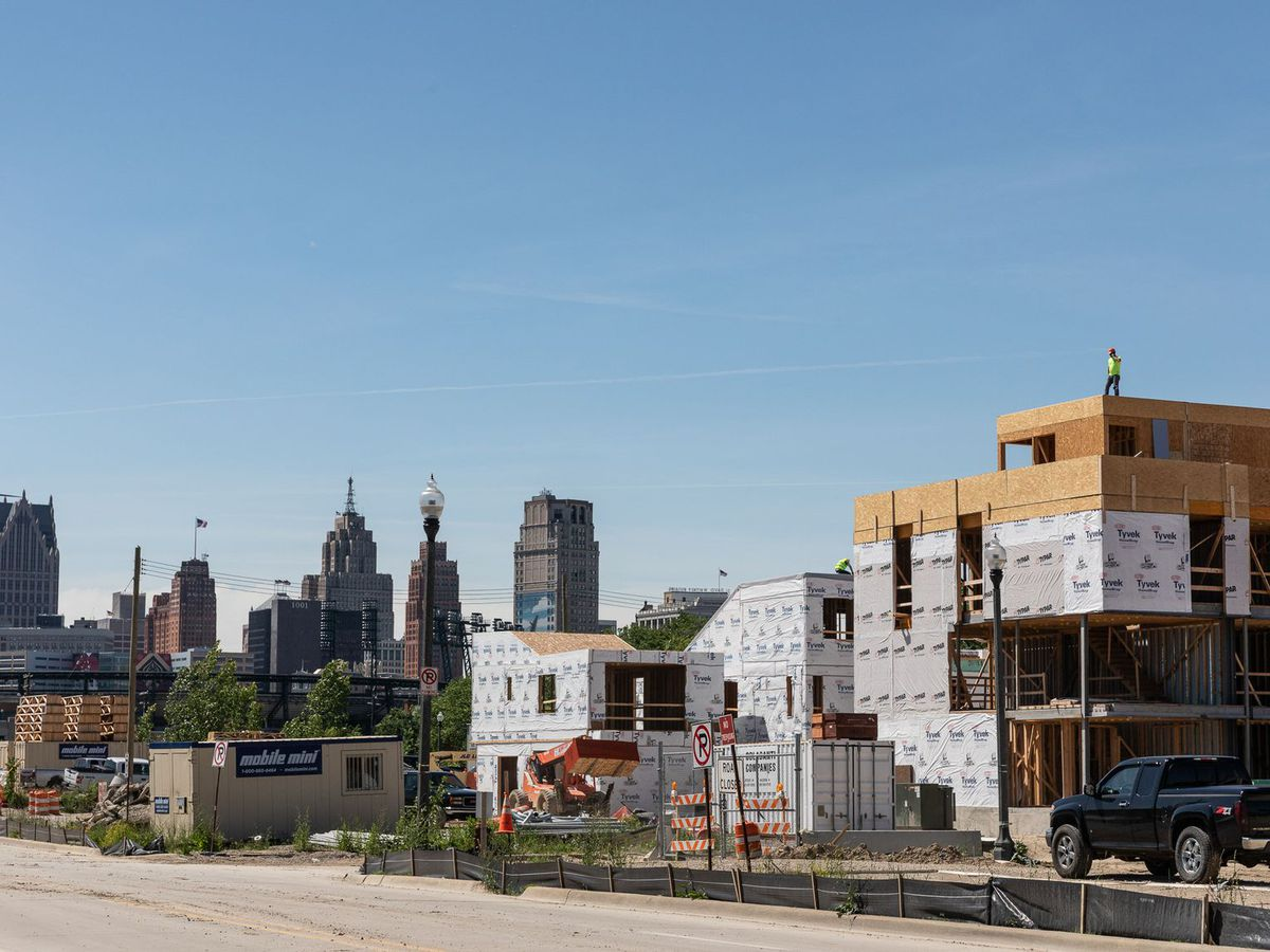 In the foreground is a construction site consisting of multiple buildings. In the distance is a city skyline with tall buildings.