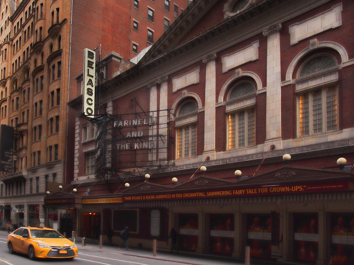 The exterior of the Belasco Theatre in New York City. The exterior is red brick and there are arched windows. There is a yellow taxi cab traveling on the street in front of the theater.