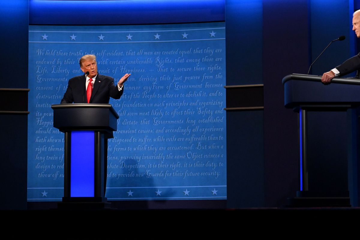 Trump, in a dark suit and red tie, raises his hand and speaks behind a blue and black podium as Biden, in a dark suit and blue tie, listens.