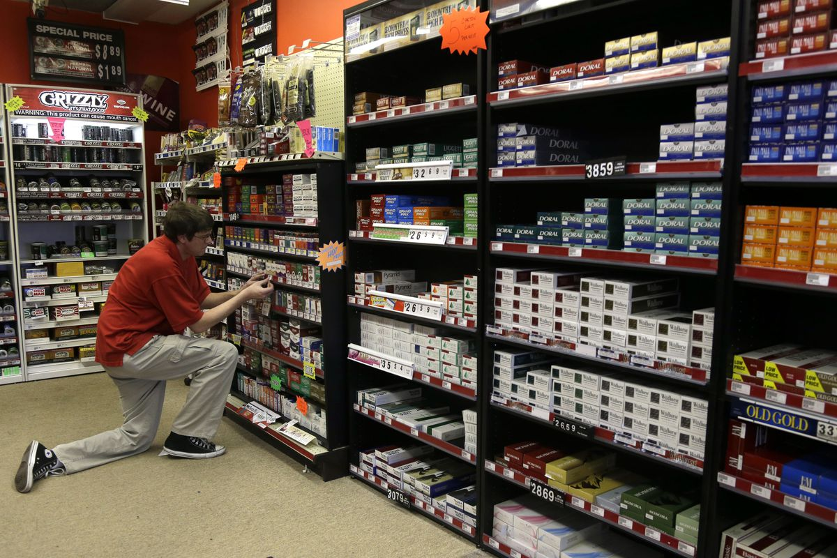A store clerk who asked not to be named places prices on a cigarette display at Discount Smoke Shop Wednesday, Oct. 31, 2012, in Ballwin, Mo. Proposition B, on the Missouri ballot Nov. 6, would funnel nearly $300 million annually for statewide public K-12