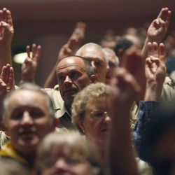Audience members raise their hands to recite the scout oath. Thousands of scouts and their leaders assemble Tuesday, Oct. 29, 2013 in the Conference Center in Salt Lake City to celebrate a century of honor.