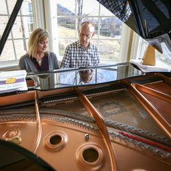 Jon and Michelle Schmidt sit and play the piano in their home in Provo on Friday, Nov. 24, 2017.