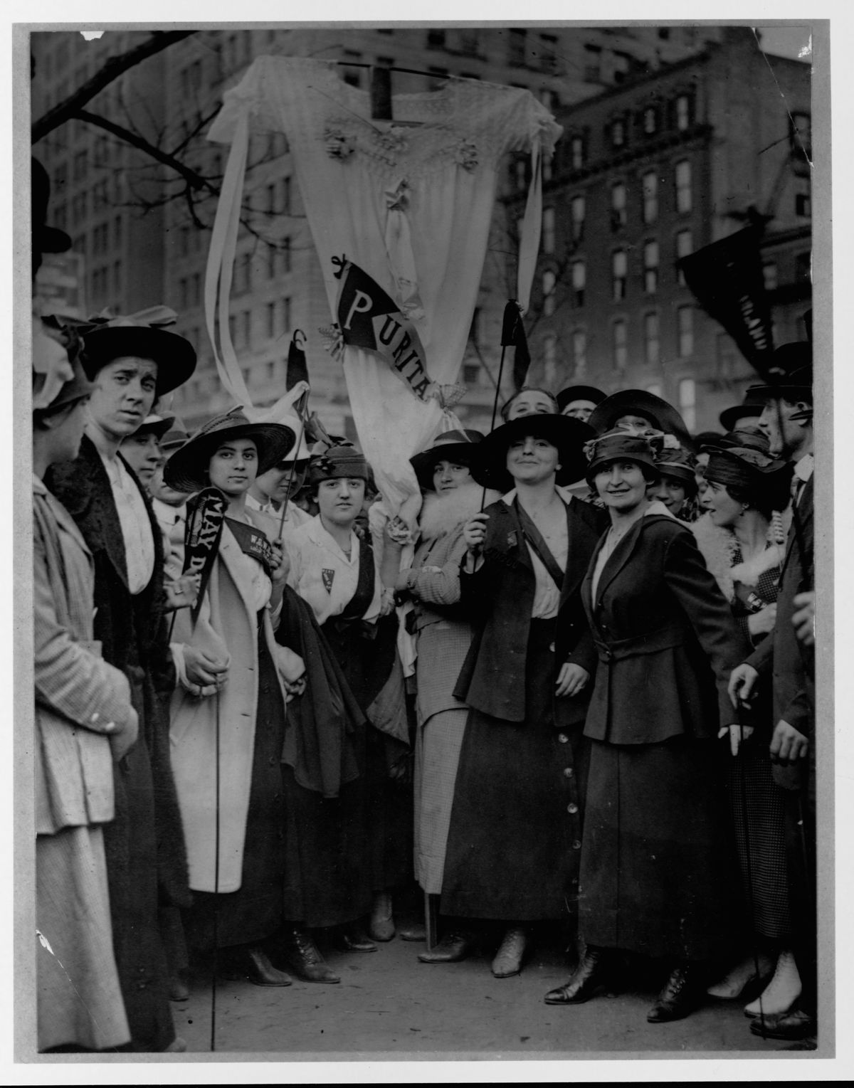 Female garment workers striking on May Day fashion a neglige as a banner. ca. 1916, New York City.   (Photo by Library of Congress/Corbis/VCG via Getty Images)