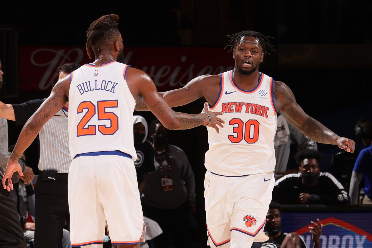 Julius Randle of the New York Knicks high-fives teammate Reggie Bullock during the game against the Atlanta Hawks on April 21, 2021 at Madison Square Garden in New York City, New York.