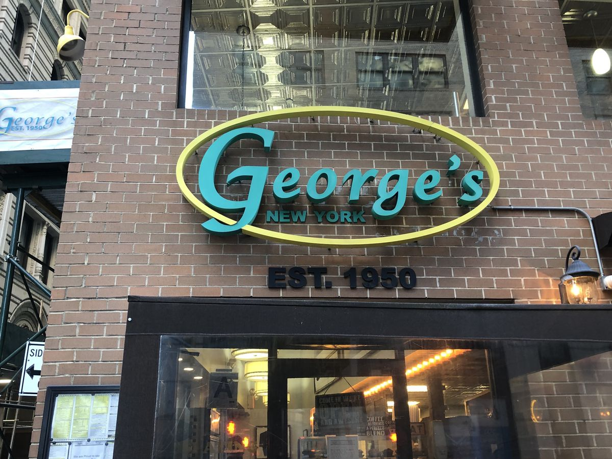 """The exterior of George's with a large restaurant sign spelling out """"George's"""" displayed over the entrance."""
