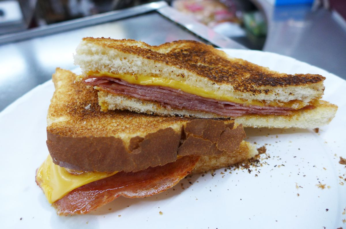 Two halves of a sandwich stacked on top of each other with crumbs strewn around.