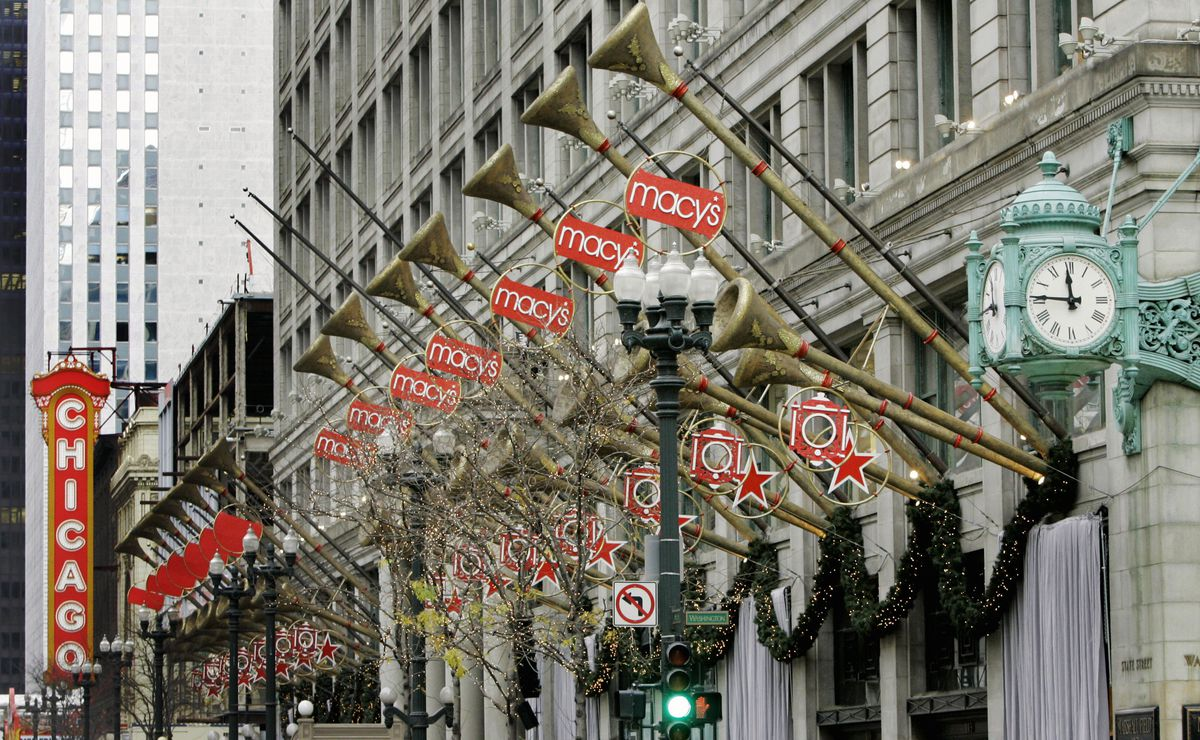 A department store's exterior decor with wreaths, lights, and a row of trumpets and red stars.