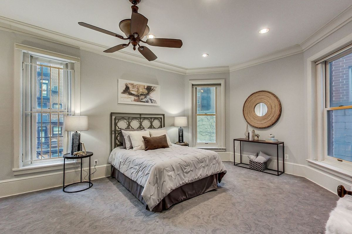 A bedroom with gray walls and carpet with three windows, a ceiling fan, and a bed against the wall.