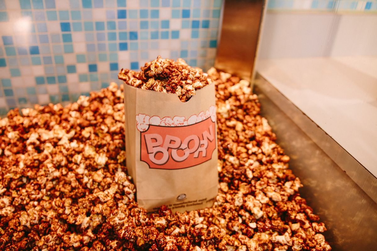 A bag of chocolate popcorn sitting on a pile of more chocolate popcorn at Cinerama.
