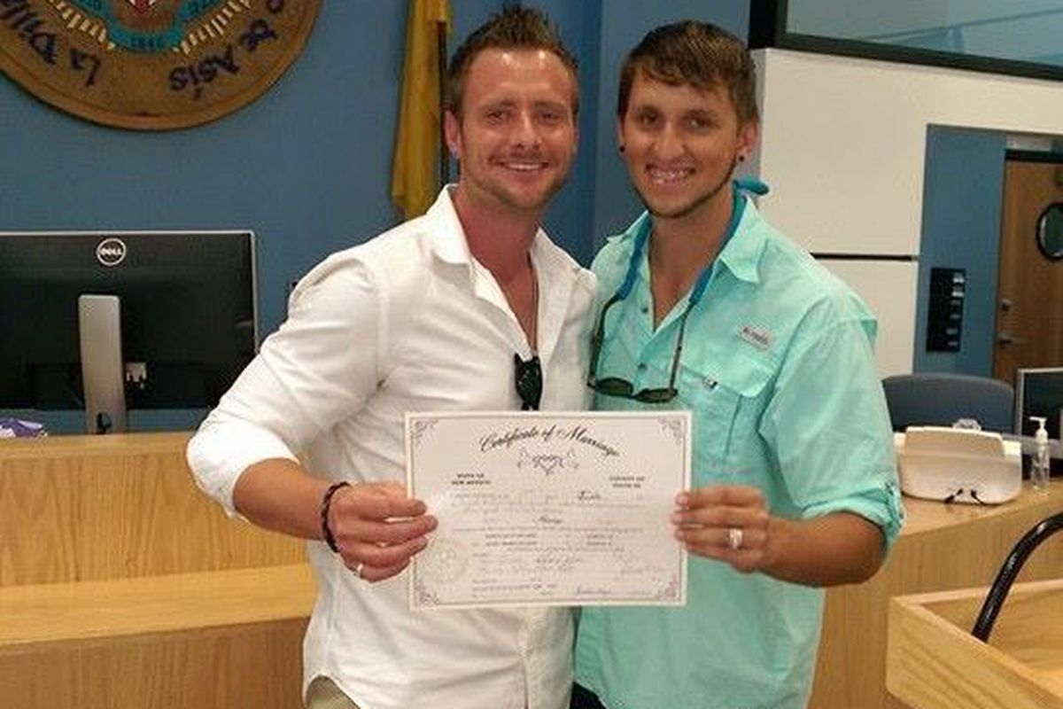 Tanner Williams, right, and Scott Williams with their marriage license in Santa Fe