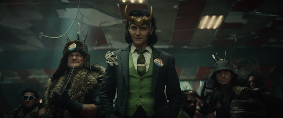 Tom Hiddleston as Loki, dressed in a ragged suit with a VOTE LOKI lapel pin, in Loki (Disney Plus)