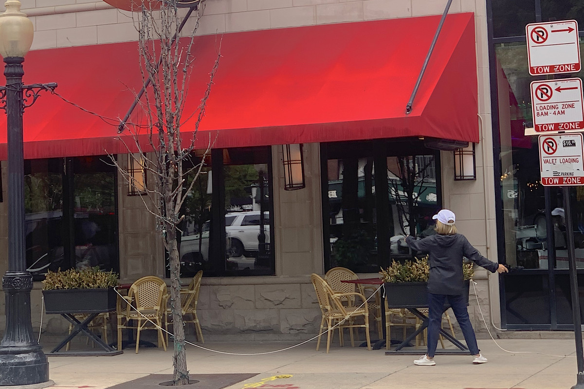 A worker at Tavern on Rush in Gold Coast sets up the patio space.