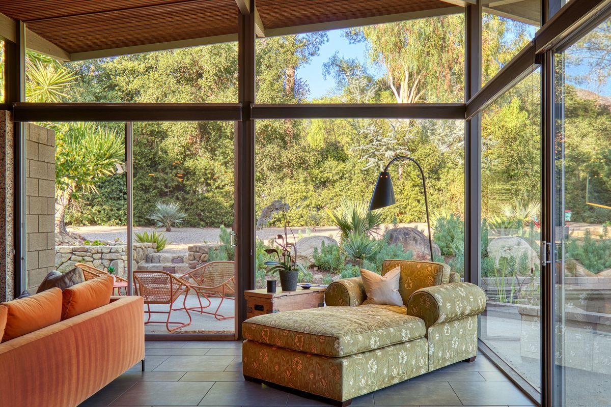 A floral-patterned chaise sits in front of two walls of glass with gardens beyond.