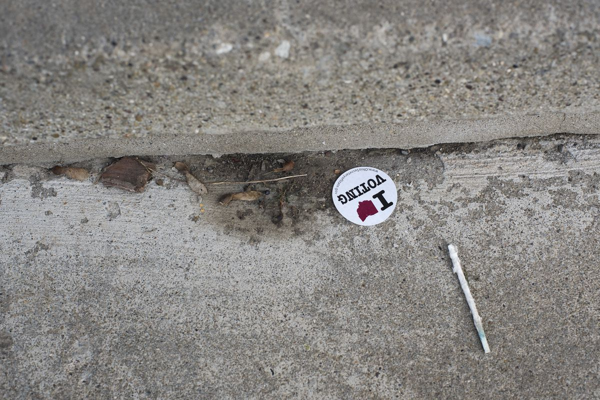 A voting sticker by a syringe.