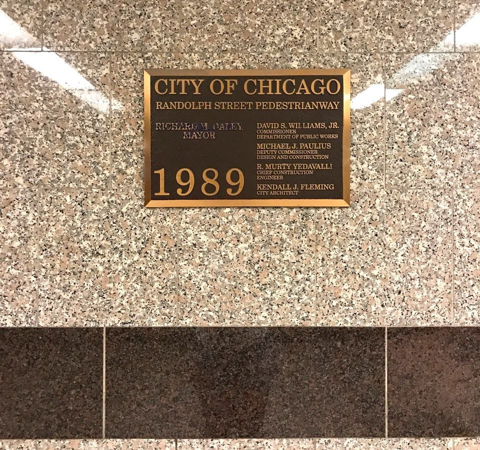 A bronze plaque on a marble wall.