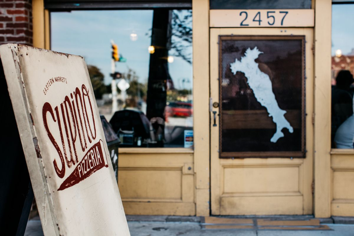 """A sandwich board reads Supino Pizza in front of the restaurant. The window to the door features a decal in the shape of Italy's """"boot."""""""