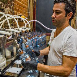 Gabe Pilato fills bottles with vodka during bottling day at Old 4th Distillery.