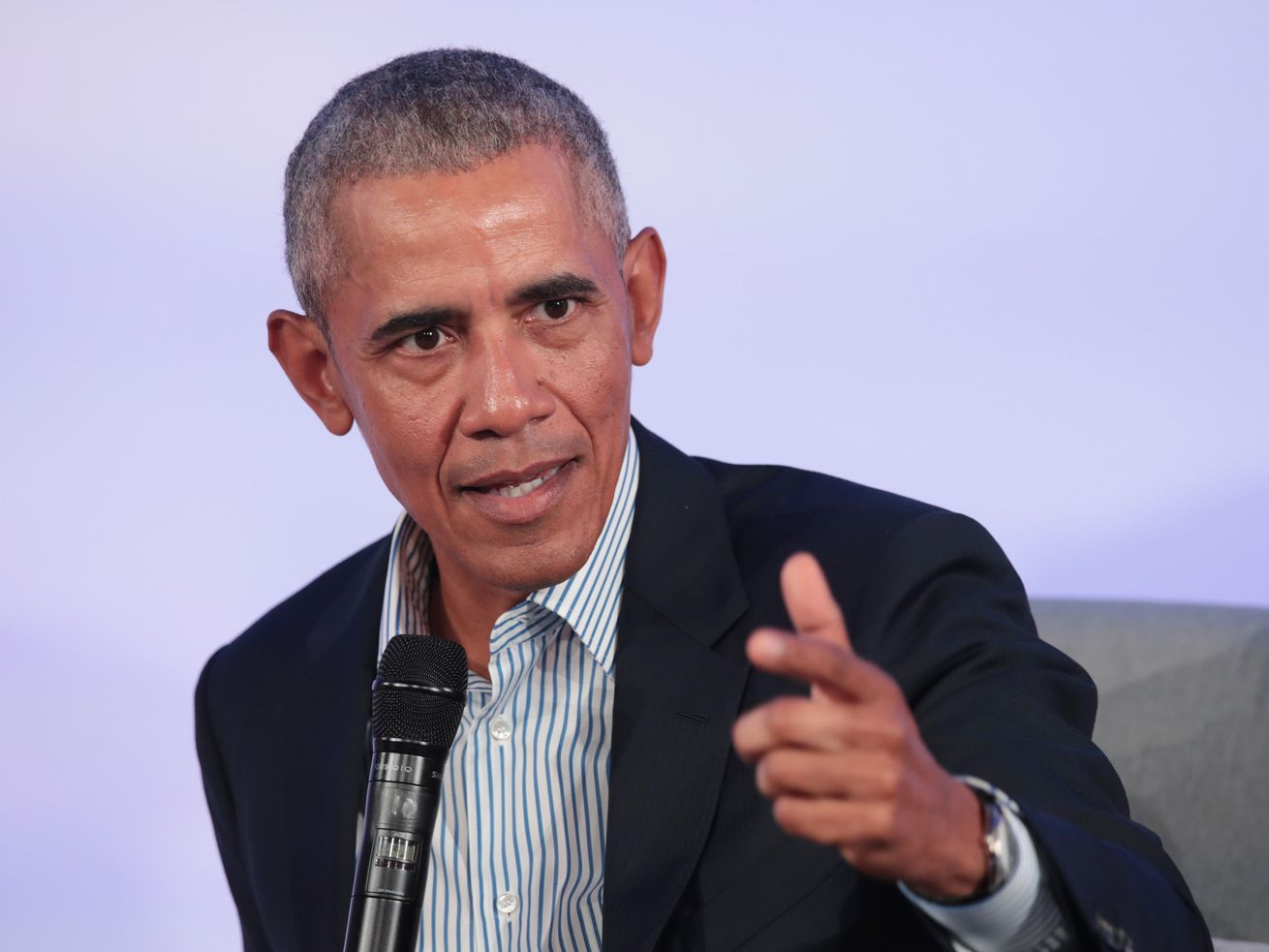 Obama, in a dark suit and blue and white button down shirt, his collar open, gestures as he speaks into a microphone.