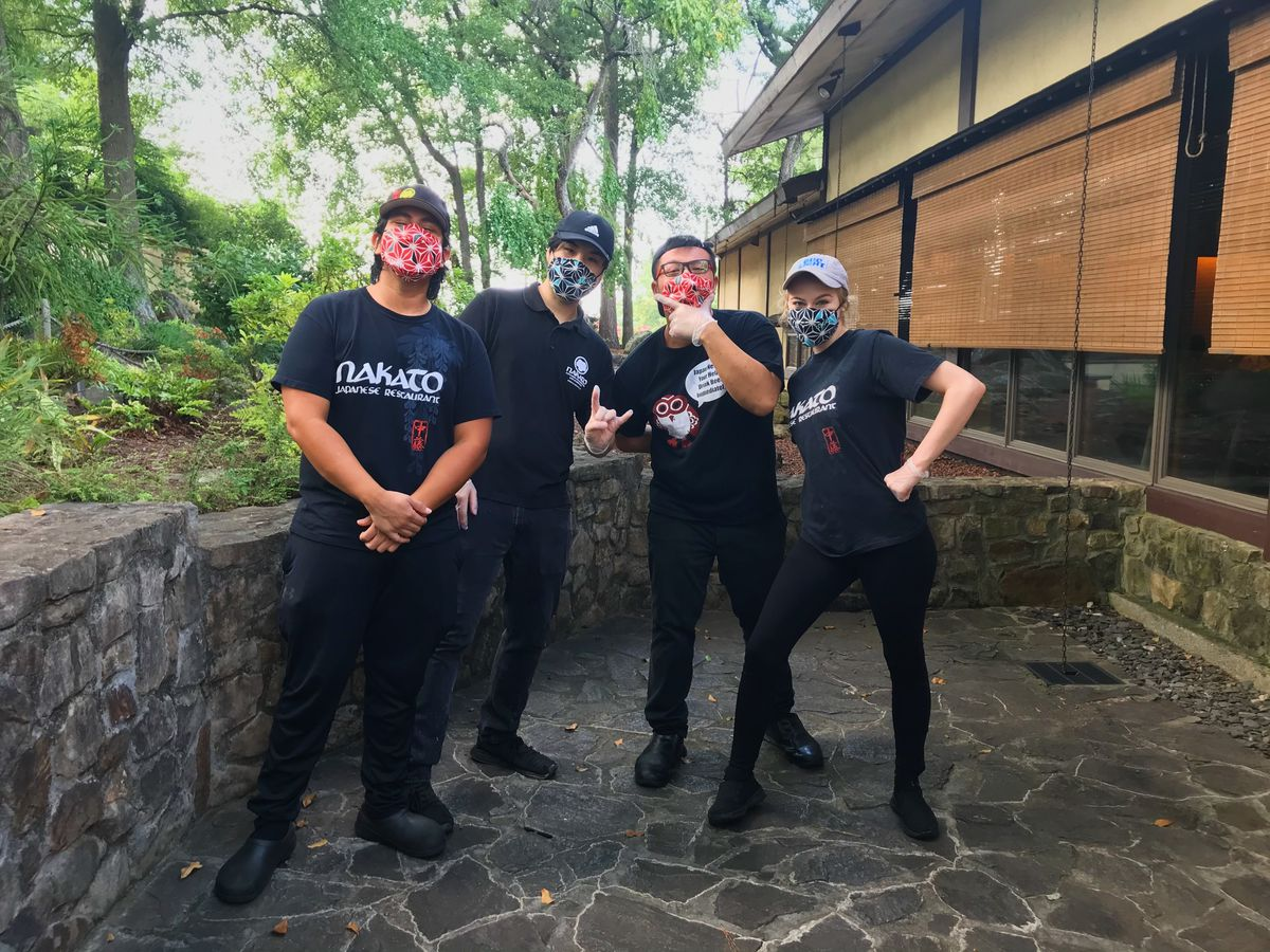 Four staff members in Nakato masks posing for the camera outside on the patio wearing black tees and black jeans