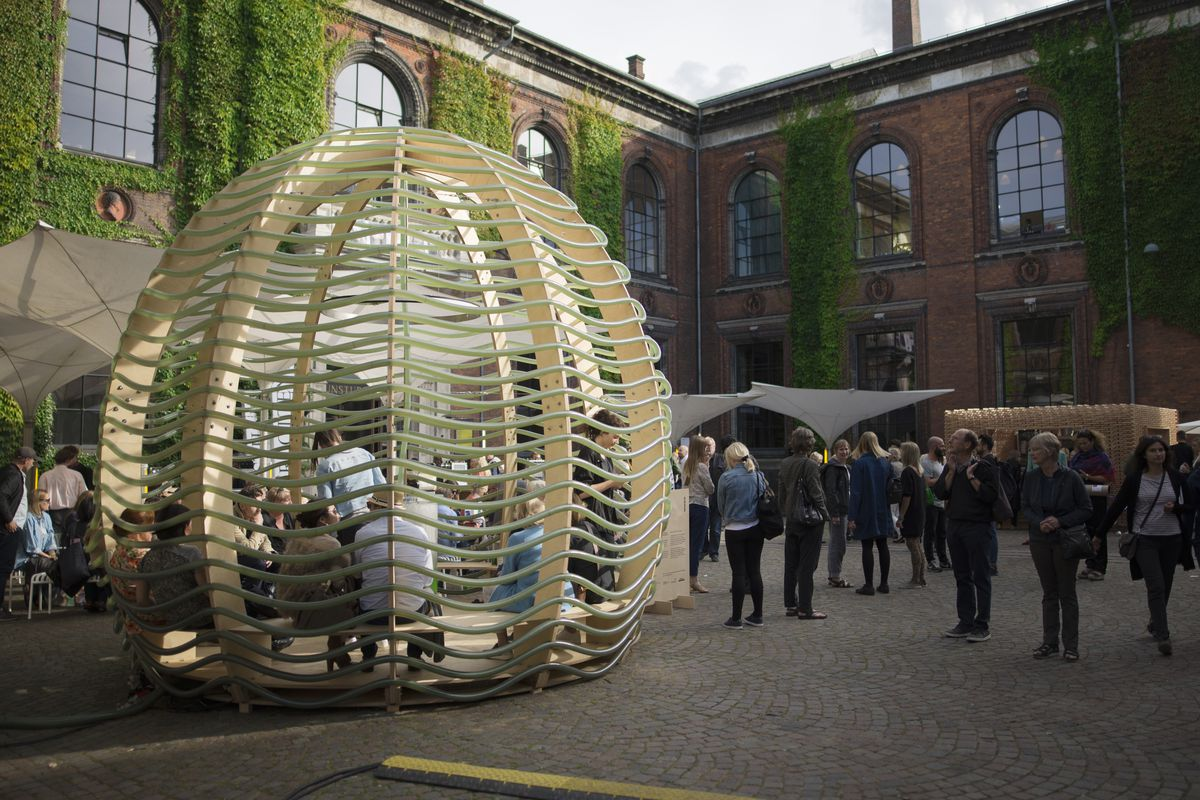 A wooden dome with open sides and clear tubing snaking around the outside sits in a town square with people bustling about.