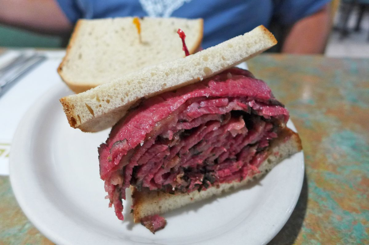 A thick pastrami sandwich a rather alarming shade of dark red.