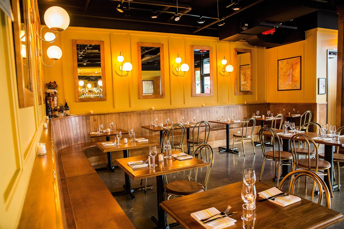A view of the warmly-lit dining room at L'Oursin, reminiscent of a French bistro, with wood-paneled booths and retro lamps.