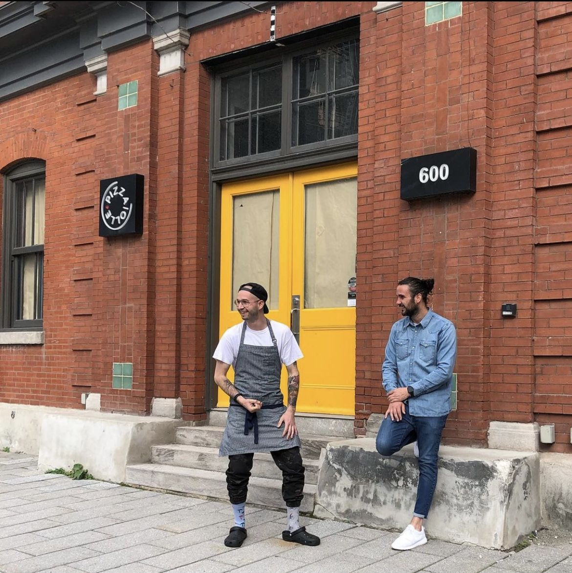 two men outside red brick building