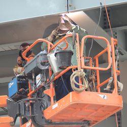 3:32 p.m. Welder working in the right-field bleachers -