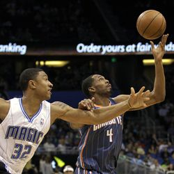 Orlando Magic's Justin Harper (32) and Charlotte Bobcats' Derrick Brown (4) go after the loose ball during the first half of an NBA basketball game, Wednesday, April 25, 2012, in Orlando, Fla.