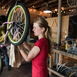 A woman works on a child's bicycle at the Provo Bicycle Collective.