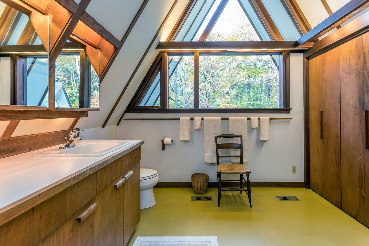 A bathroom has white counters, wooden cabinets, a green floor, wooden closet, and triangle windows.