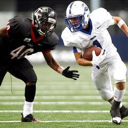 Bingham's Brady Measom, right, tries to avoid the tackle of Euless (Texas) Trinity defender Dante Charleston after making a catch as Bingham and Trinity play at Dallas Cowboys Stadium Monday in Arlington, Texas. Trinity won 42-21 in the Kirk Herbstreit Varsity Football Series.