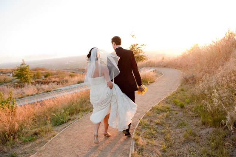 A man and a woman walk down a dirt path. The path is surrounded by shrubs and grass. There is a sunset in the sky. The man is in a black suit. The woman is in a white wedding dress.